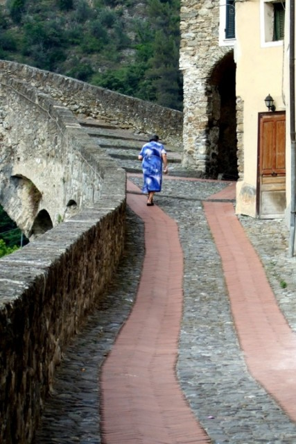 Woman walking uphill in Dolceacqua, in Liguria - photo by Margie Miklas