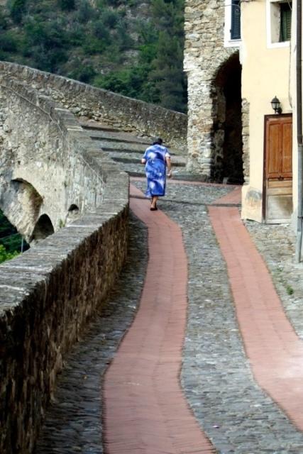 Woman walking uphill in Dolceacqua, in Liguria - photo by Margie Miklas