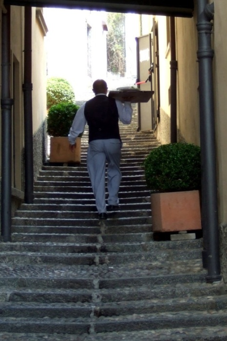 Waiter carrying a tray up a staircase in Bellagio, Italy