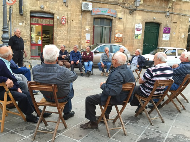 Local Italian men in Squinzano, Puglia discussing important issues of the day ~ Photo by Margie Miklas